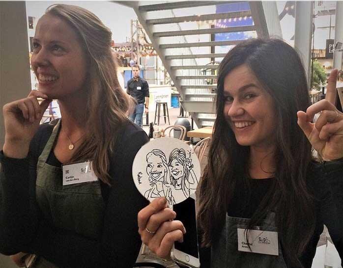 2 meisjes poseren. 1 meisje met donker haar houdt een bierviltje vast met een karikatuur tekening van de meisjes samen