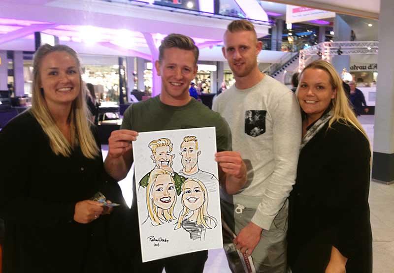 4 mensen zijn getekend als karikatuur op 1 vel papier met markers, pen en krijt. Ze staan als held op de cartoon getekend door de sneltekenaar