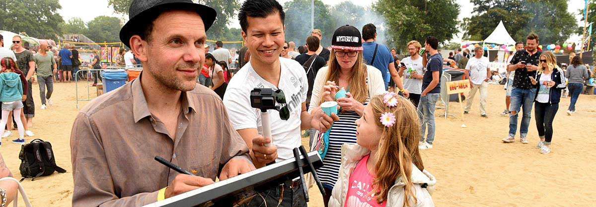 sneltekenaar tekent op het festival stran een karikatuur op een bierviltje van oo onbekend persoon. Publiek filmt.