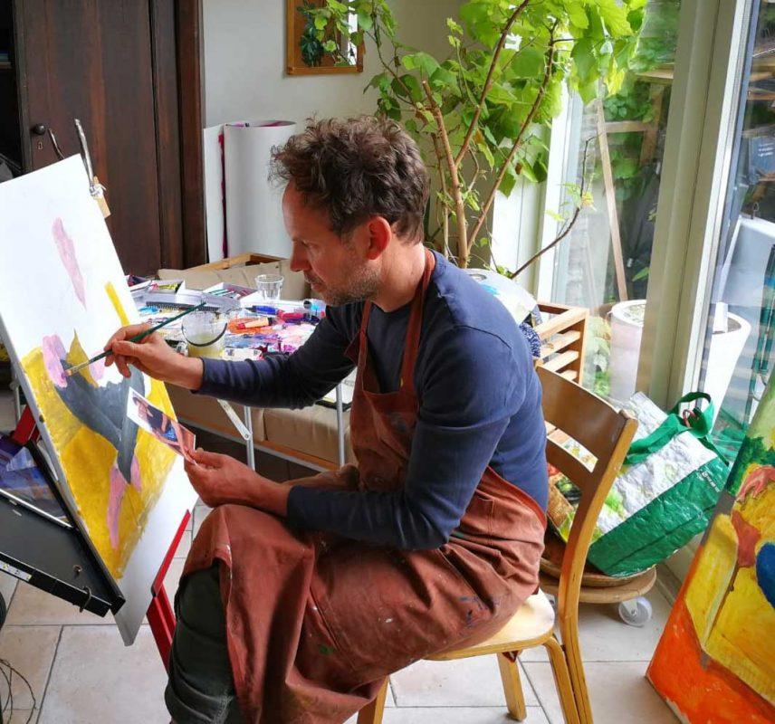 Portretschilder in atelier zit op een stoel met een penseel in zijn hand en schildert met acrylverf een schilderij . Het is een portret van een jongen in de stijl van Gauguin.